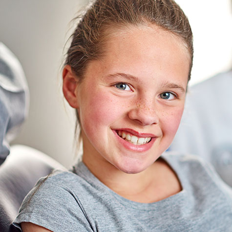 Tween girl smiling at camera from dental chair